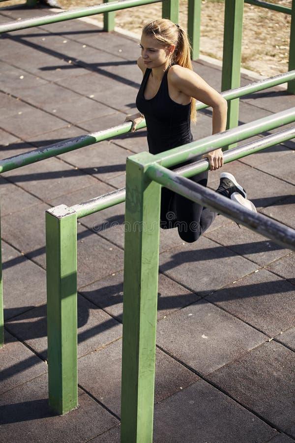 一年轻女人,20-29年,行使户外在公园,室外健身房,做引体向上,增加, 免版税库存照片