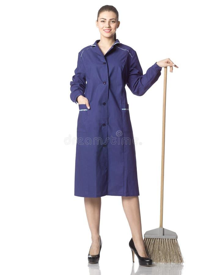 一年轻妇女擦净人站立与在一件蓝色长袍的一把笤帚 库存照片