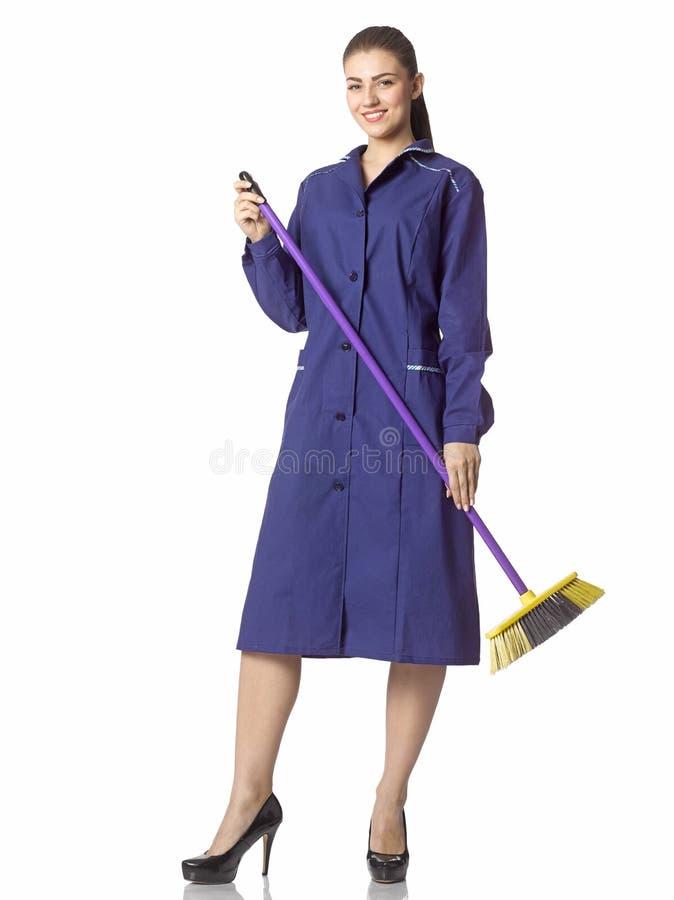 一年轻妇女擦净人站立与在一件蓝色长袍的一把笤帚 图库摄影