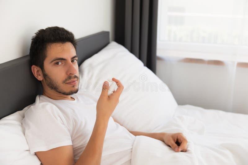 一年轻帅哥在他的床上坐 库存图片