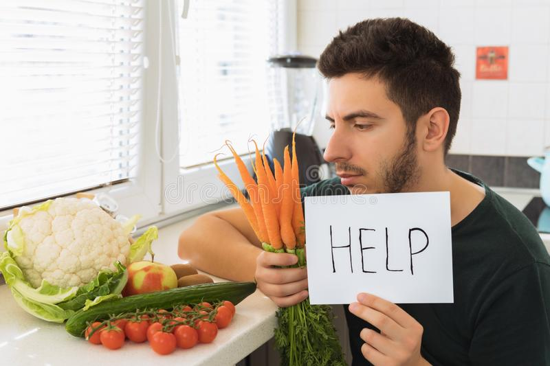 一年轻帅哥在有一张恼怒的面孔的厨房里坐并且请求帮忙 免版税库存照片
