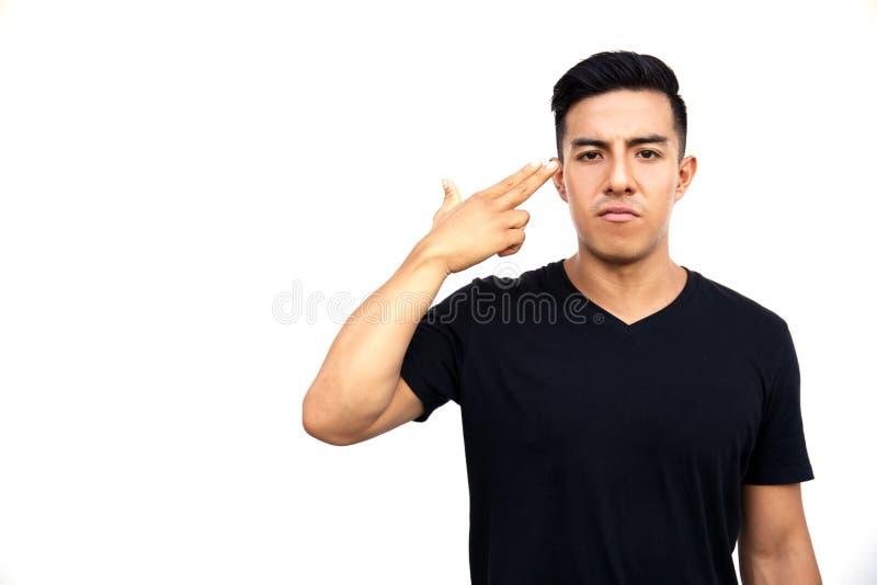 一年轻拉丁帅哥的画象有两个手指的对他的头 图库摄影