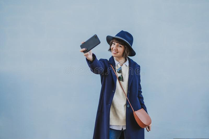 一年轻美女的画象户外有摆在与一个现代帽子和采取与手机的时髦的衣裳的一selfie 库存照片