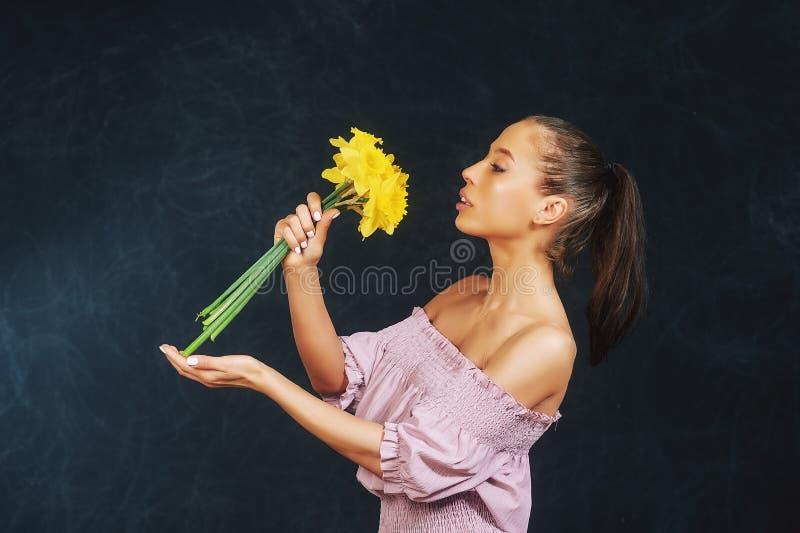 一年轻美女的画象有花的在演播室 库存照片