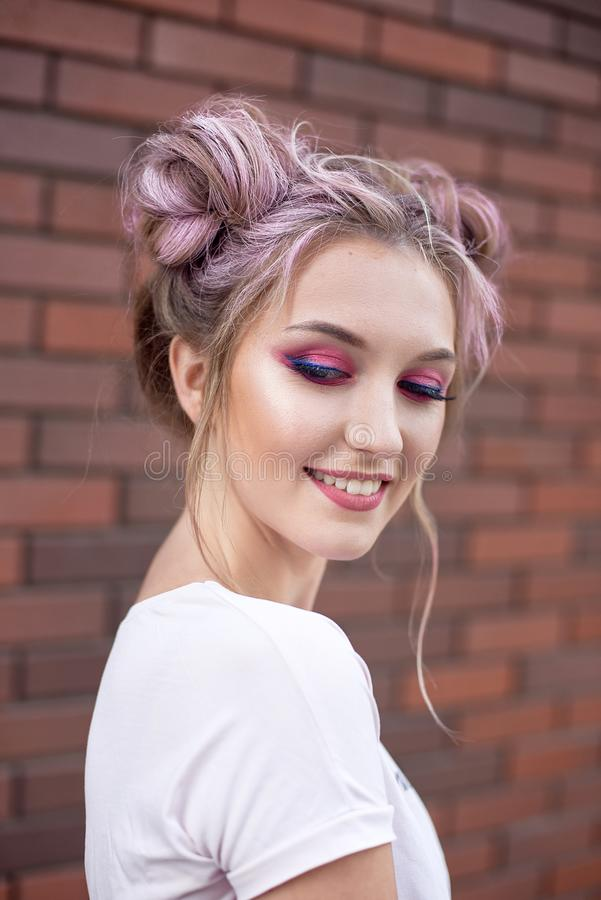 一年轻美女的画象用桃红色头发小圆面包 微笑对红砖墙壁的明亮的桃红色构成 免版税库存图片