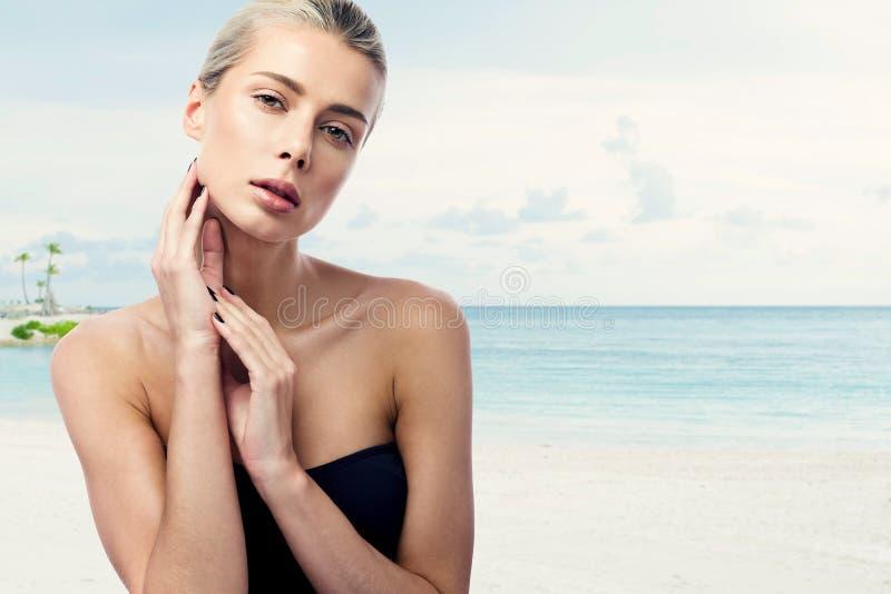 一年轻美女的秀丽画象反对海的 黑泳装和金发 免版税图库摄影