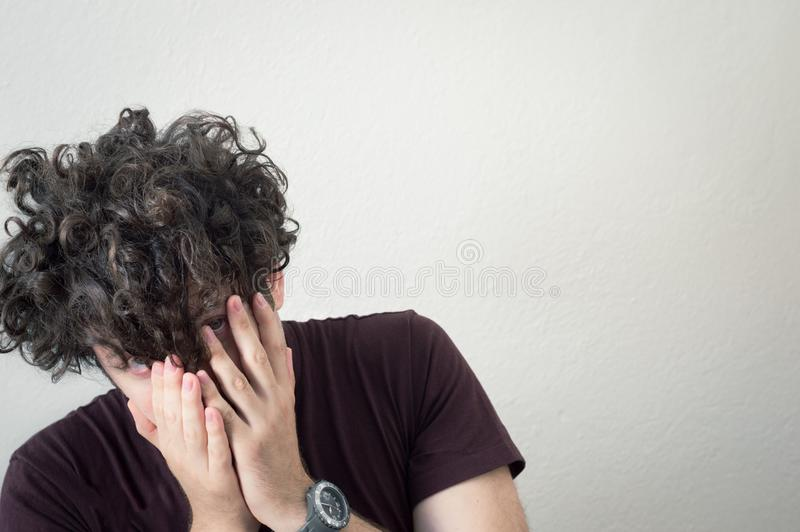 一年轻,白种人,深色,卷发的人coverin的画象 库存照片