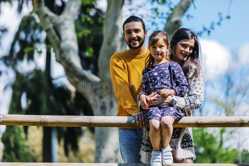 一幸福家庭的正面图在公园 一起父亲母亲和儿子本质上看照相机的 免版税库存照片
