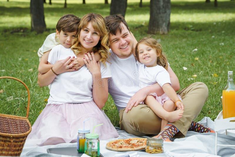 一幸福家庭的画象一顿野餐的在一个晴朗的夏日 免版税库存照片