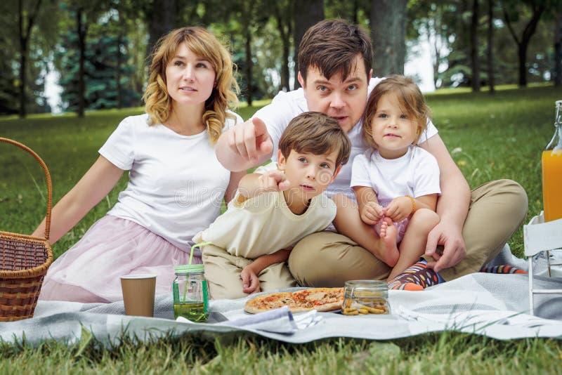 一幸福家庭的画象一顿野餐的在一个晴朗的夏日 免版税库存图片