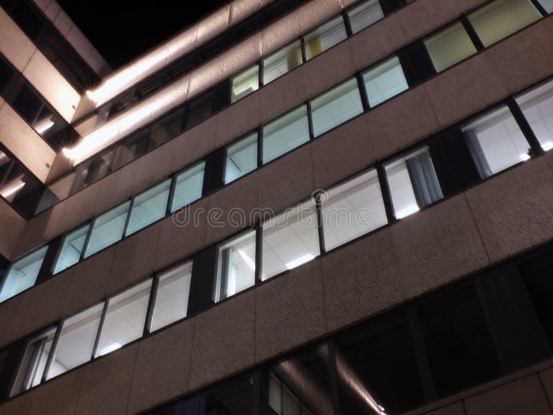 一座办公楼的角落在与有启发性发光在外部门面的墙壁和光的晚上 免版税库存图片