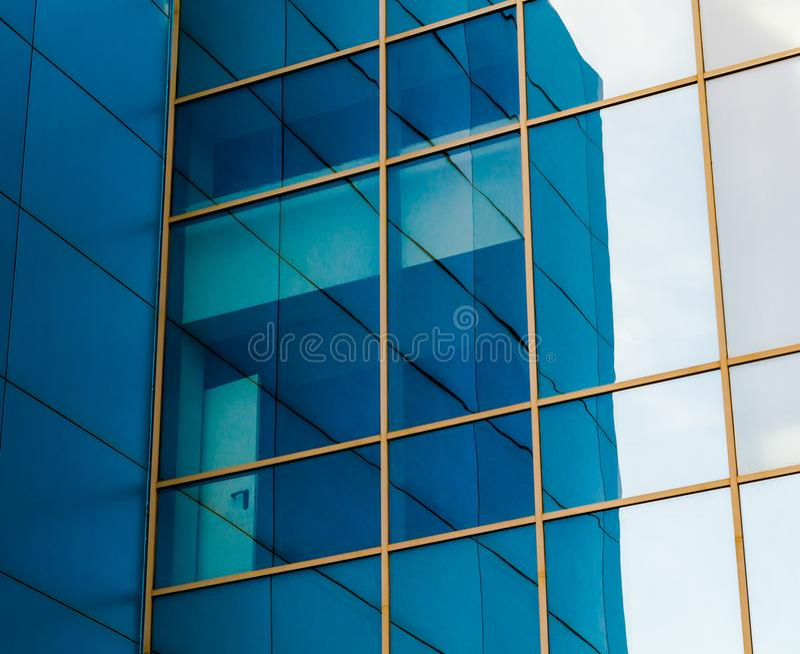 一座办公楼的门面的被反映的窗口与蓝色盘区和黄色窗架的与被变形的反射  免版税库存图片