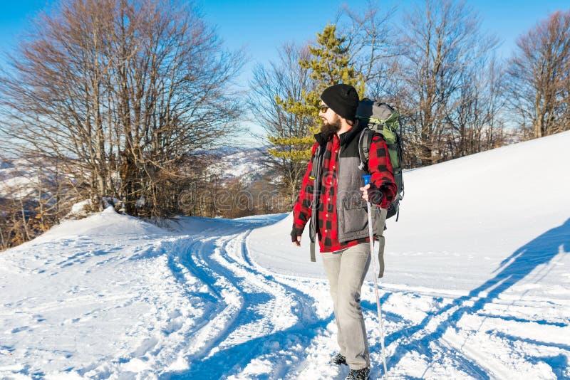 一座多雪的山的有胡子的男性远足者 库存图片