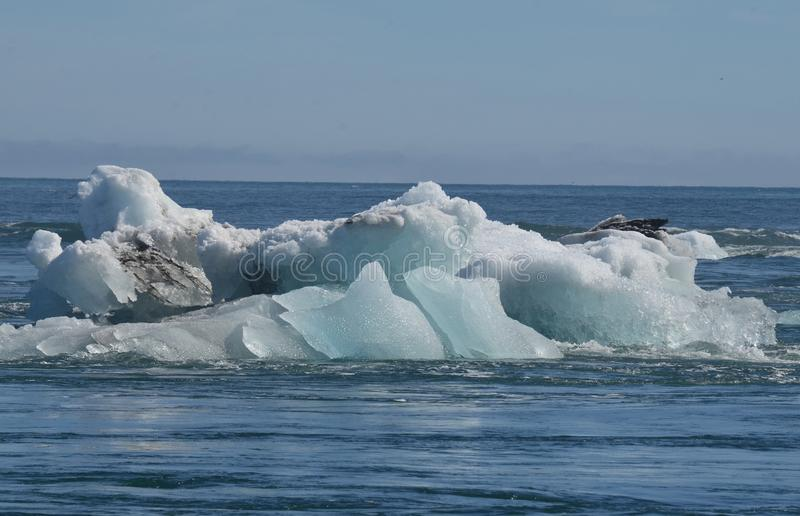 一座大冰山的惊人的看法与沉积的在盐水湖 图库摄影