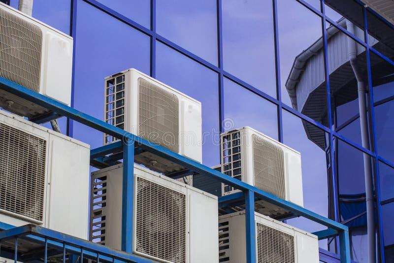 一座大办公楼的墙壁与蓝色窗口和空调的 免版税库存图片