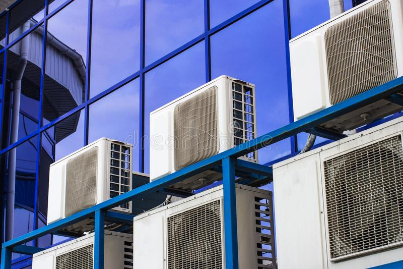 一座大办公楼的墙壁与蓝色窗口和空调的 免版税库存照片