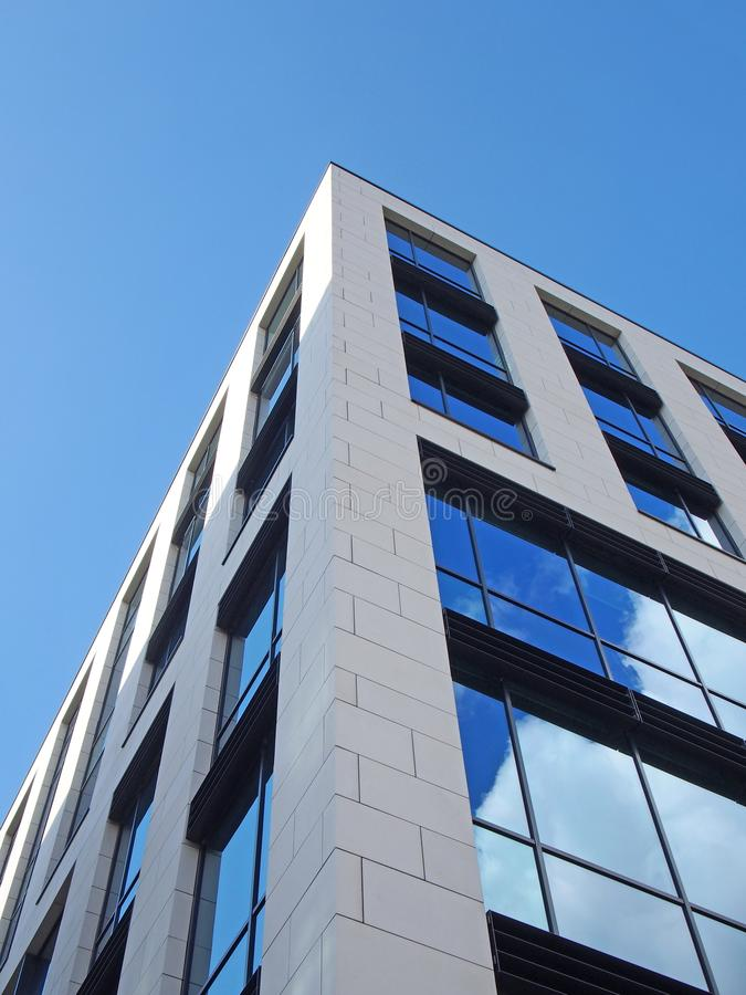 一座白色现代办公楼的角落的向上看法与在大玻璃窗和云彩的反映的天空蔚蓝 免版税库存照片