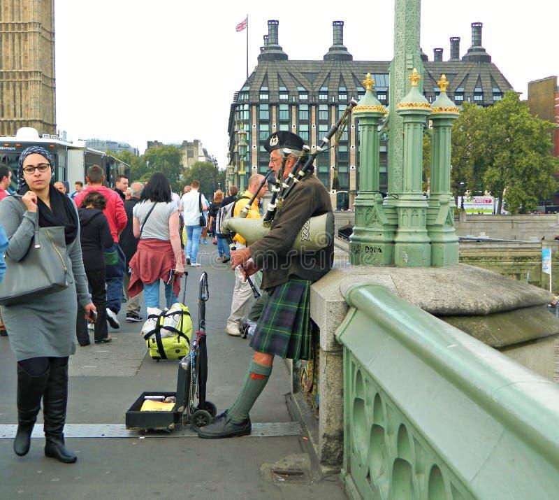 一座繁忙的威斯敏斯特桥梁的苏格兰风笛球员在伦敦 库存照片