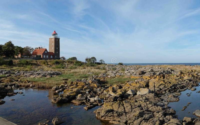 一座老灯塔由砖做成近由海洋 当您在海岛博恩霍尔姆时,旅行您能找到这座灯塔 库存照片