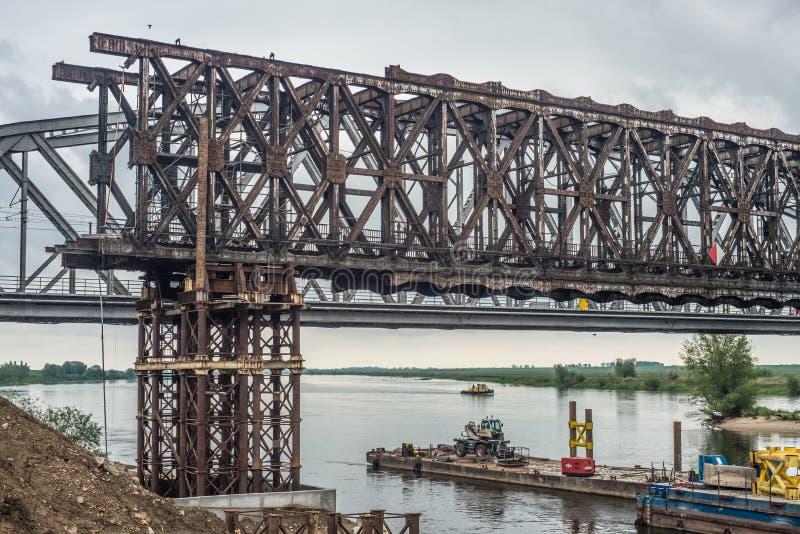 一座老钢桥梁的拆卸在一座新的桥梁的工地工作 库存图片