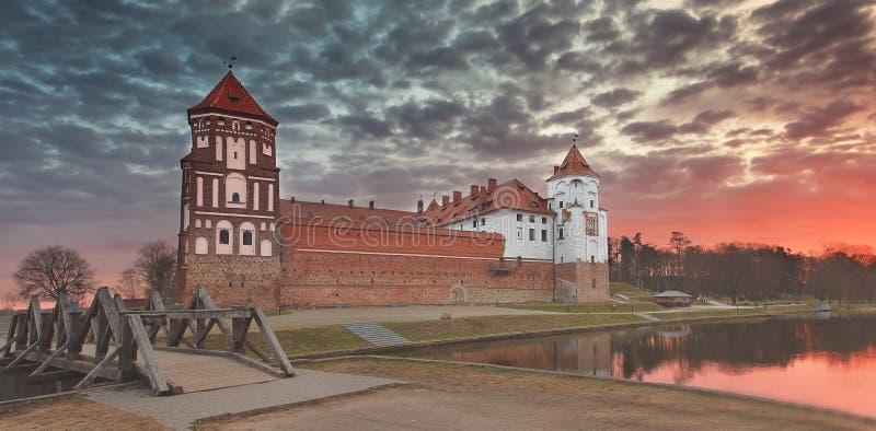 一座老Mir城堡的风景反对五颜六色的天空的在美好的黎明 库存图片