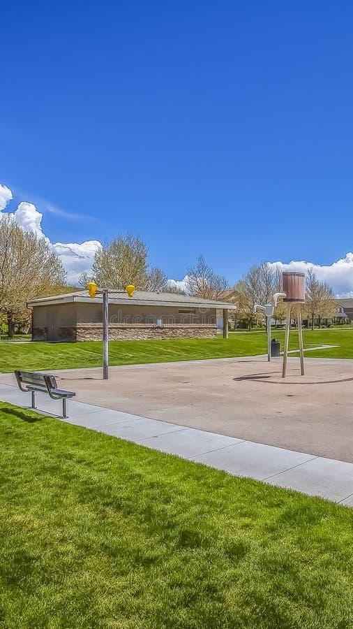 一座豪华的领域俯视的山树和大厦的垂直的公园反对天空蔚蓝 免版税库存图片