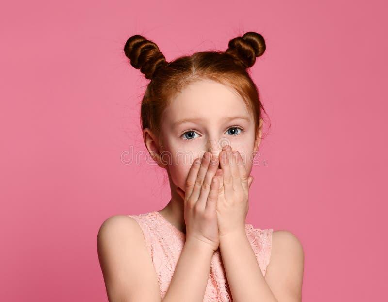 一张严肃的年轻姜女孩覆盖物嘴的画象用保留秘密的两只手 图库摄影