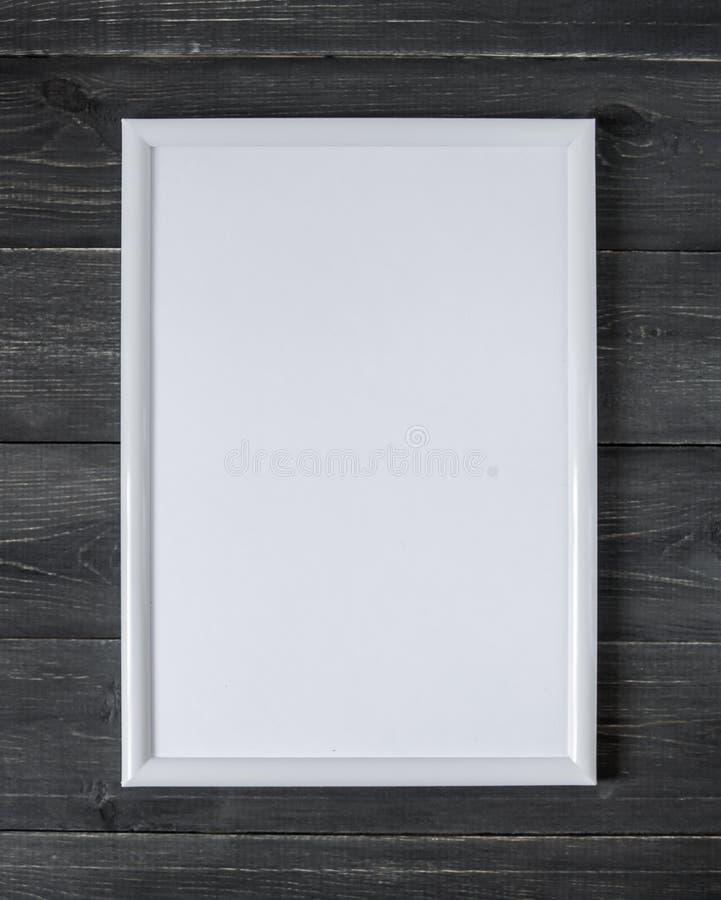 一张图片的空的白色框架在黑暗的木背景 免版税图库摄影