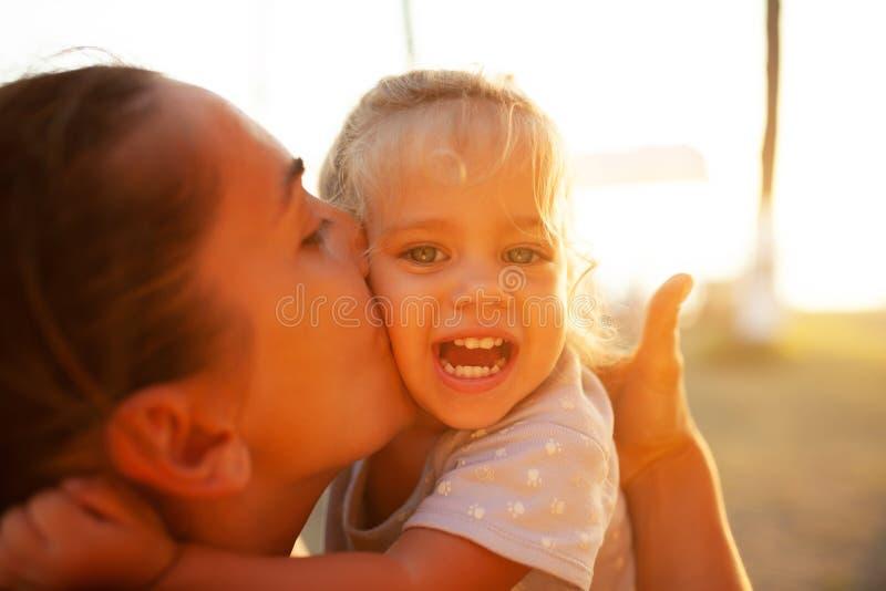一张大画象,母亲亲吻她的落日的光芒的女儿 家庭价值观,愉快的孩子 免版税库存图片