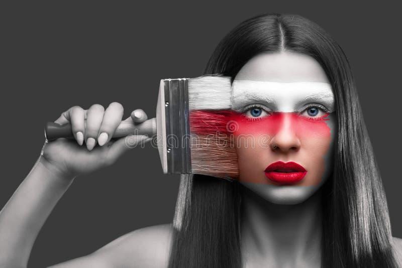 一张妇女绘画的画象与一把刷子的在她的面孔 免版税库存图片