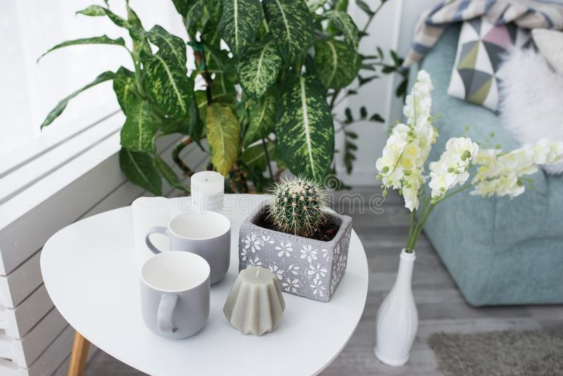 一张小加奶咖啡桌用仙人掌、一个灰色蜡烛和杯子 免版税库存图片