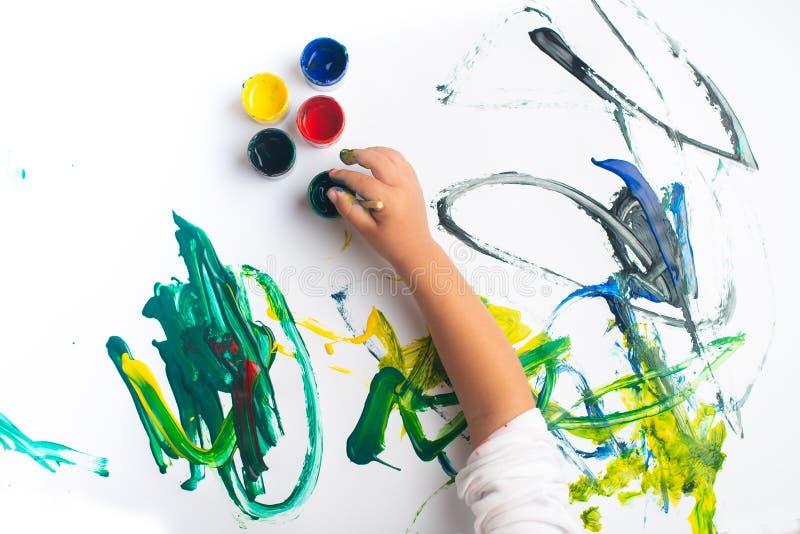 一张小男孩绘画的手与水彩的在白皮书板料 有刷子和五颜六色的油漆的小男孩 r 免版税库存照片