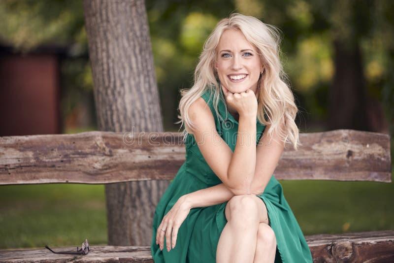 一张少妇画象,坐在木长凳,绿色礼服, 25岁,微笑愉快,看对照相机 免版税库存图片
