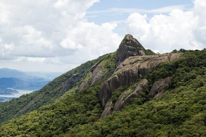 一张山岩石面孔的水平的看法与有些树的在与白色云彩的蓝天下- pico e serra做lopo 免版税库存图片
