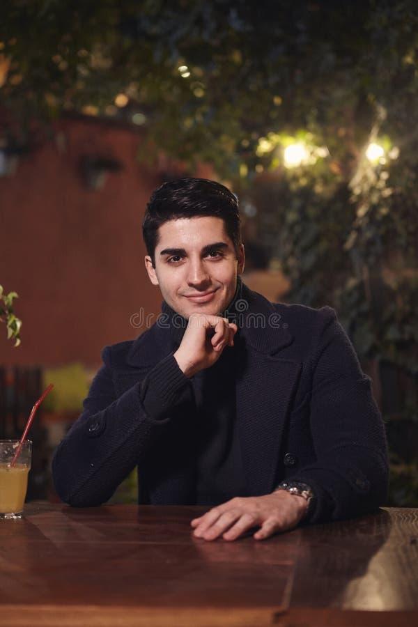 一张年轻帅哥画象,坐在咖啡馆庭院里在桌上,夜户外,看对照相机 上身射击 库存照片