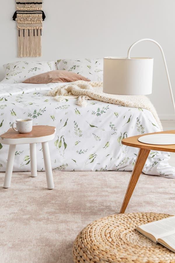 一张床的舒适淡色卧室站立在软的桃子的内部与坐垫的和亚麻布上色地毯 实际照片 库存图片
