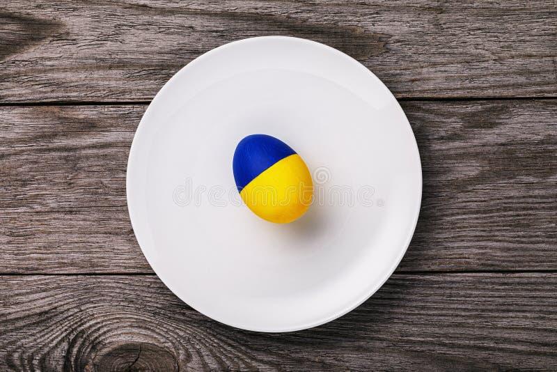 一张彩绘乌克兰国旗的复活节彩蛋,放在木桌上的白色陶瓷板上。一张彩绘乌克兰国旗的复活节彩è 免版税库存照片