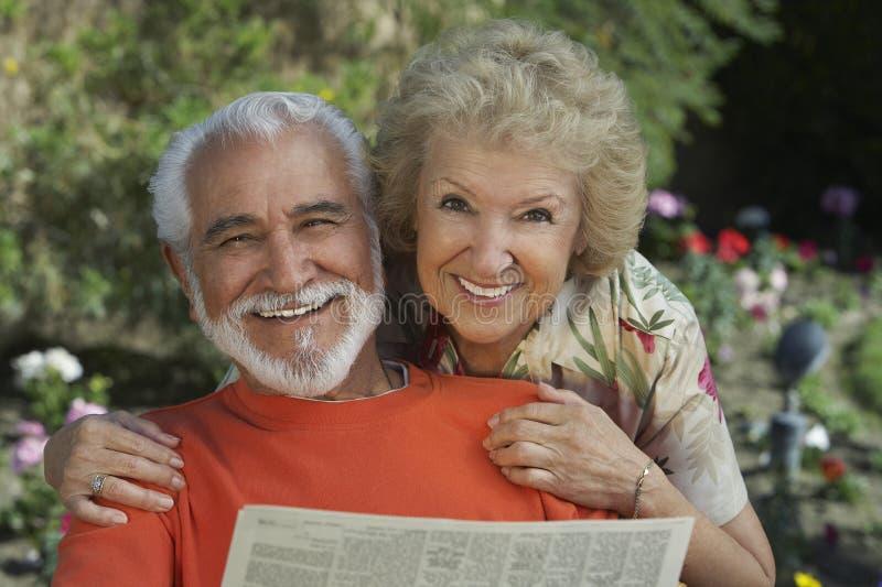 一张愉快的资深夫妇读书报纸的画象 免版税库存图片