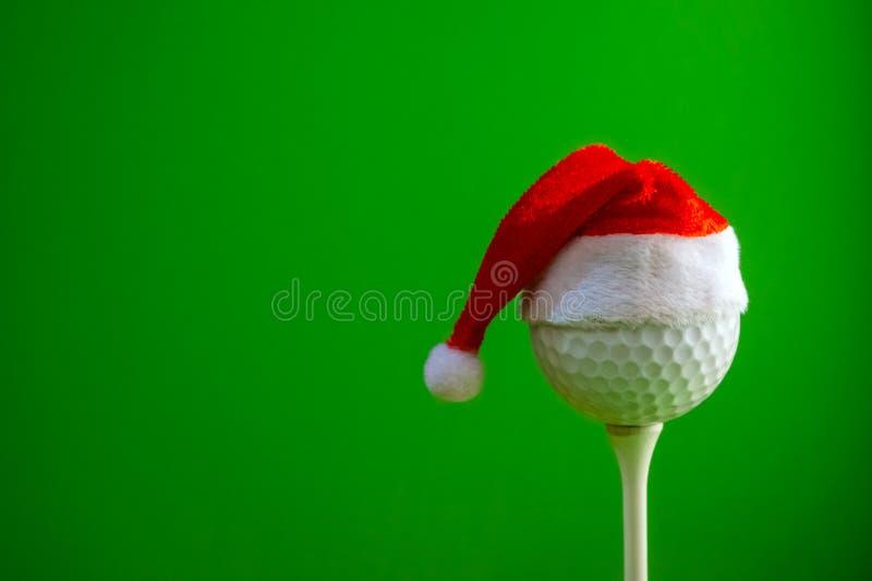 一张明信片的设计的空白一位高尔夫球运动员的新年或圣诞节 在一个发球区域的高尔夫球与一个红色圣诞老人项目帽子 免版税库存照片
