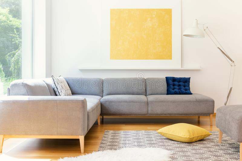 一张最低纲领派,黄色海报和白色、工业落地灯在晴朗的客厅内部与一个被仿造的地毯和充满活力的de 库存照片