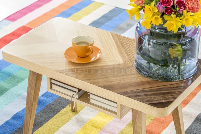 一张木桌的特写镜头与一杯咖啡和花束的  库存图片