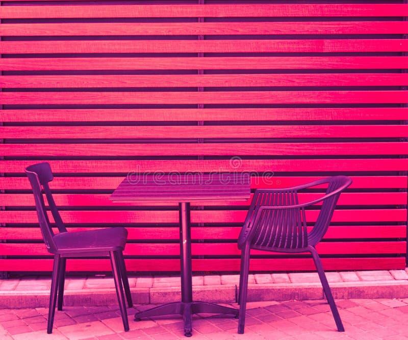 一张桌和两把椅子从木板在街道上站立在城市s咖啡馆在夏天 免版税库存图片