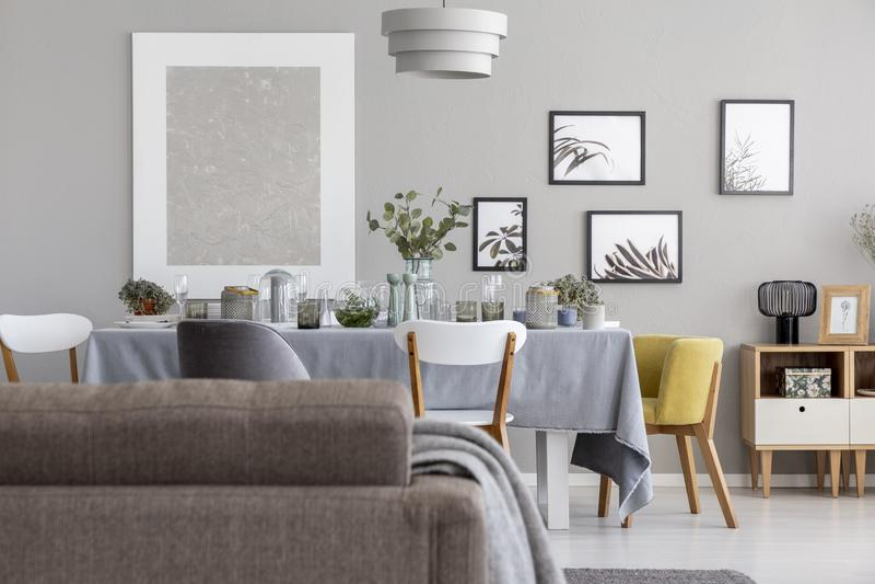 一张沙发和餐桌与碗筷和图表在墙壁上在每日室内部 图库摄影