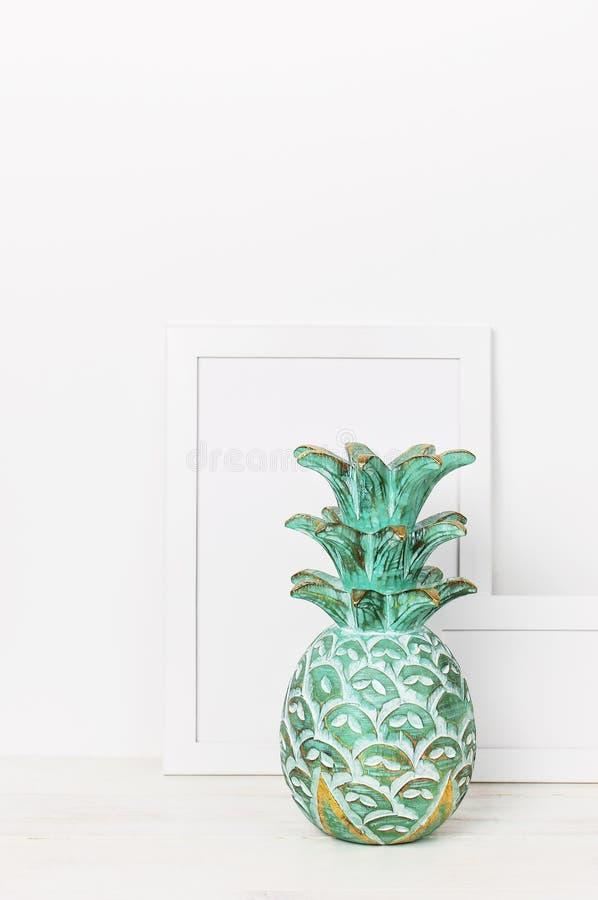 一张照片和一个木鲜绿色菠萝的木空的框架在白色墙壁的背景 白纸框架,现代家de 图库摄影