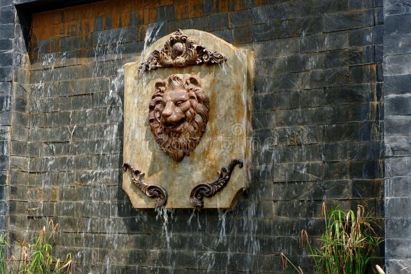 一张狮子面孔的雕象在复制品瀑布的 免版税库存图片