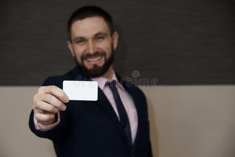 一张空的卡片在一个被弄脏的有胡子的年轻人的手上有微笑的在西装 免版税库存图片