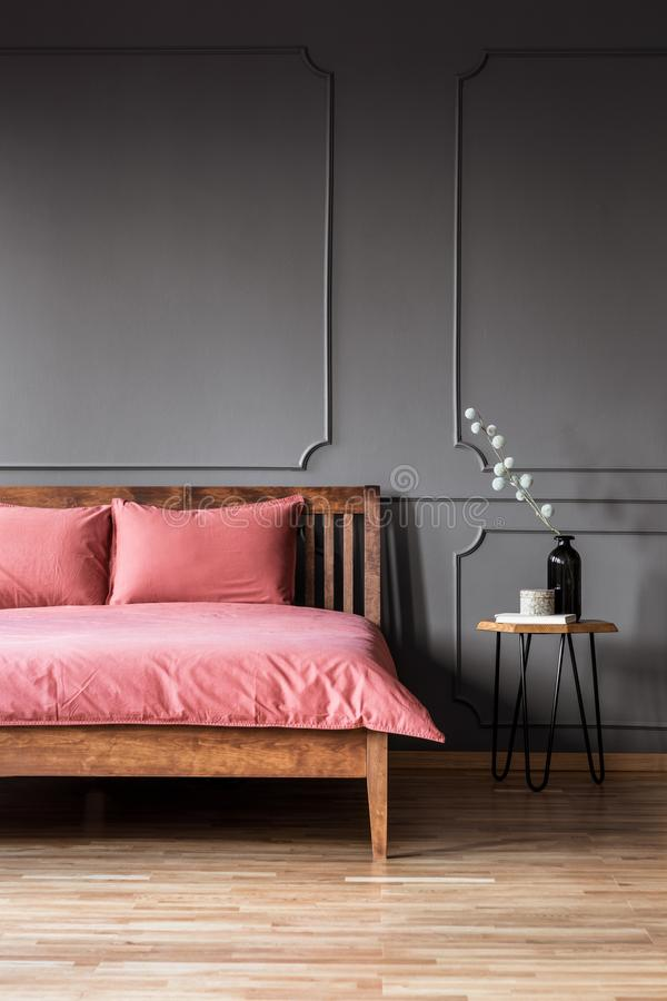 一张简单和典雅的床的真正的照片与肮脏的桃红色卧具n的 库存图片