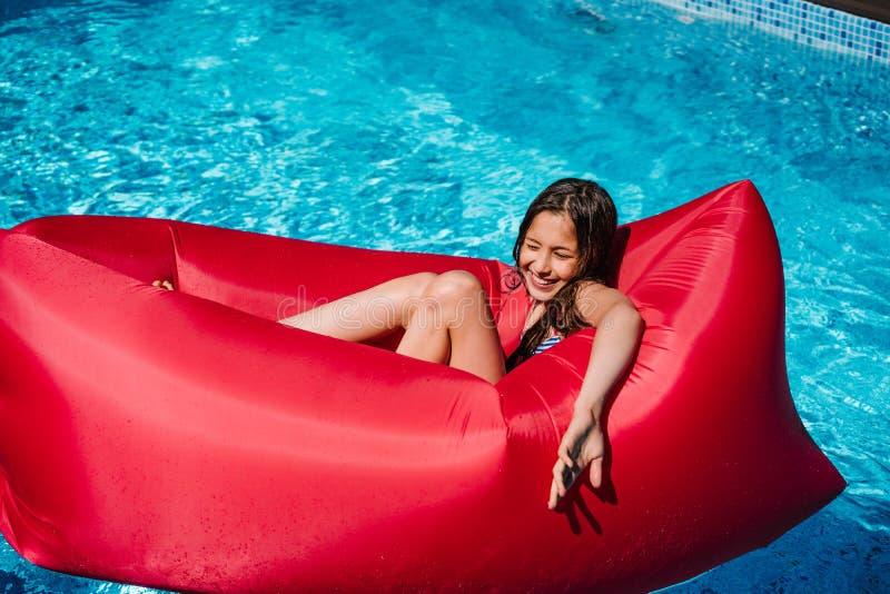 一张红色躺椅的青少年的女孩 免版税图库摄影