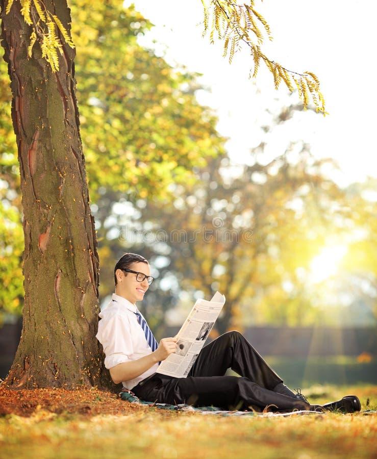 一张草读书报纸的年轻人在一个公园在一个晴天 库存图片