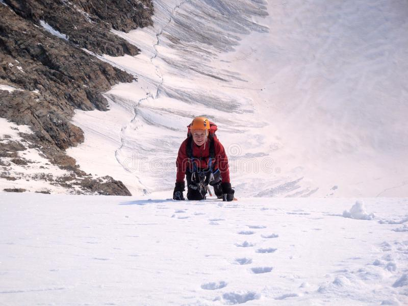 一张陡峭的北部面孔的女性登山人到达一个高山峰顶的山顶 免版税库存图片